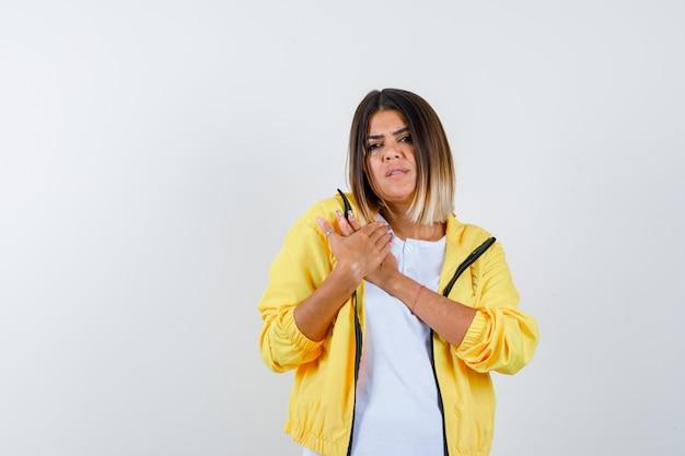 Mulher mantendo as mãos no peito em t-shirt, jaqueta e parecendo triste, vista frontal.