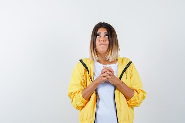 Mulher mantendo os dedos entrelaçados na camiseta, jaqueta e parecendo indecisa, vista frontal.