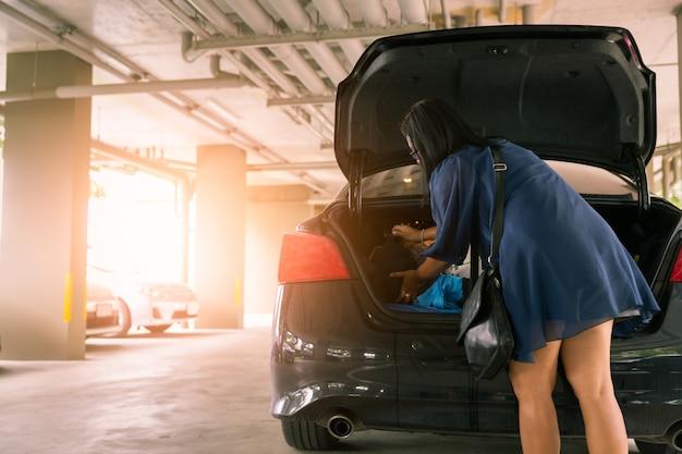 Mulher, mantenha, saco, em, tronco carro, em, lote estacionamento