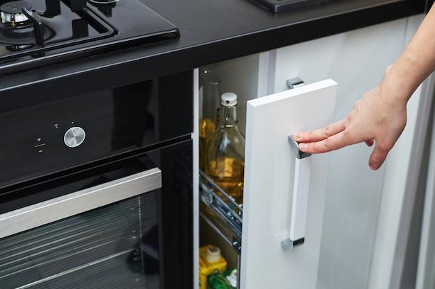 Mulher mão aberta armário de armazenamento de cozinha no interior moderno