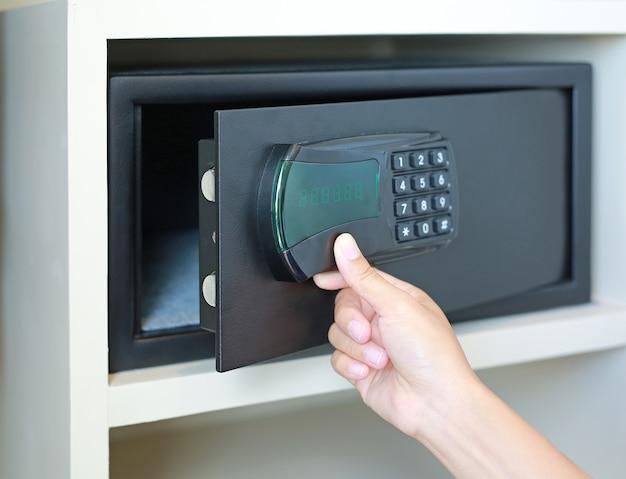 Mulher mão abre um cofre escondido no guarda-roupa do hotel.