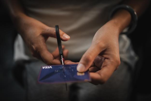 Mulher mão corte ouro cartão de crédito com tesoura.