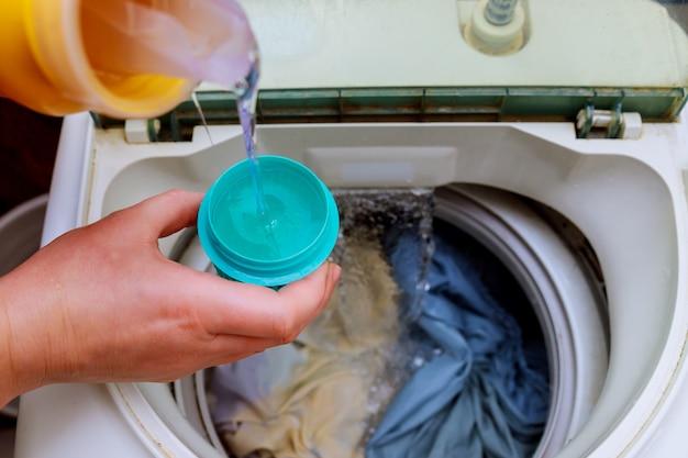 Mulher mão derramando sabão em pó na máquina de lavar roupa