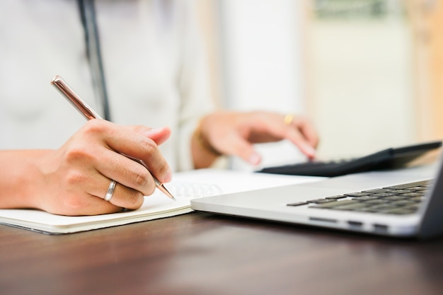 Mulher mão escrevendo no caderno e pressionando na calculadora no escritório