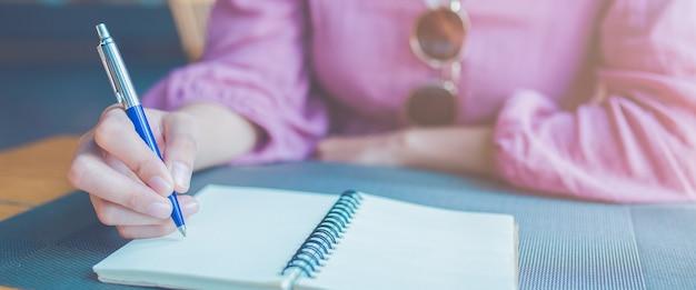 Mulher mão está escrevendo em um bloco de notas com uma caneta