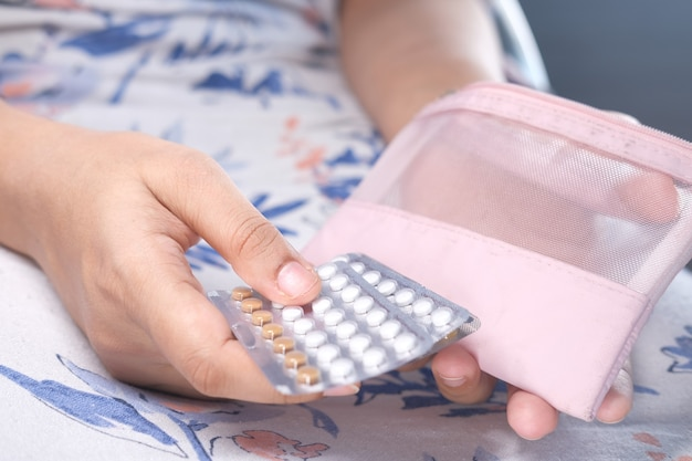 Mulher mão golding pílulas anticoncepcionais close-up