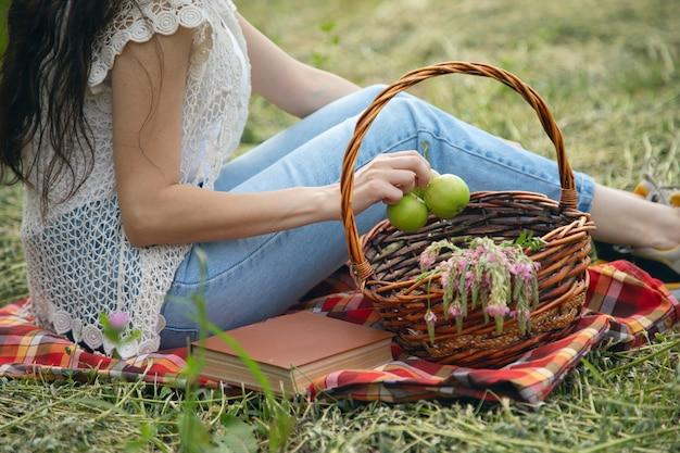 Mulher mão maçã e cesta sentada no campo