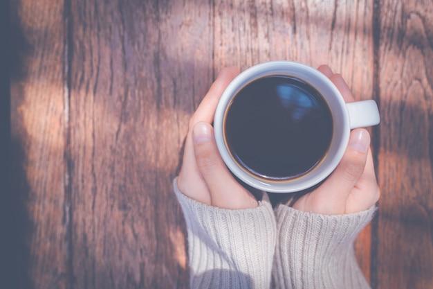 Mulher mão no suéter quente segurando uma xícara de café em um fundo de mesa de madeira, vista superior