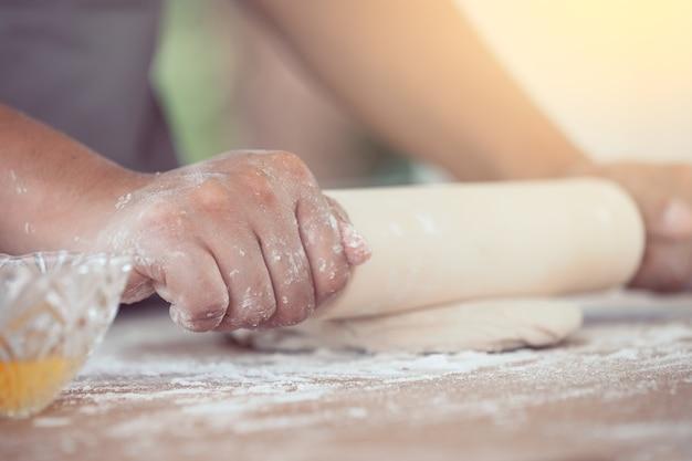 Mulher mão preparando massa de pão para assar biscoitos na cozinha em tom de cor vintage