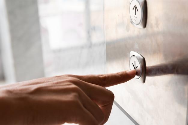 Mulher mão pressione um botão para baixo do elevador