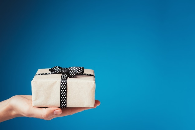 Mulher mão segura a caixa de presente na palma da mão sobre fundo azul, com espaço de cópia