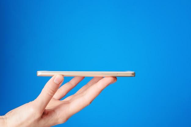 Mulher mão segura smartphone em fundo azul