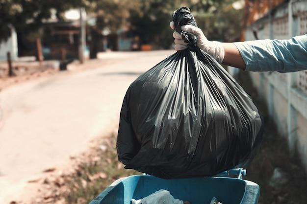 Mulher, mão, segurando, lixo, saco preto, ponha, em, lixo