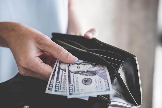 Mulher mão segurando moeda americana de cinco notas de dólar, gastos e compras para o desejo humano, w