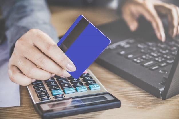 Mulher mão segurando o cartão de crédito fazendo o pagamento