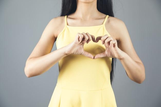 Mulher mão sinal de coração cinza