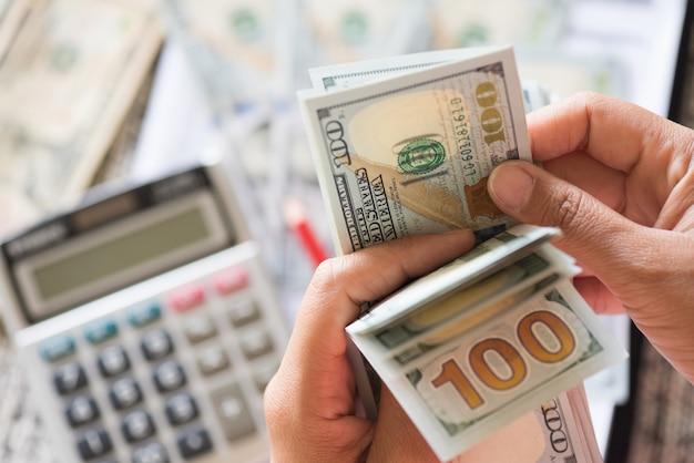 Mulher, mãos, contagem, grupo, de, américa dólares, notas, calculadora, e, lápis vermelho, em, backg