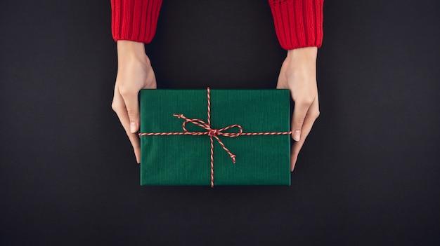 Mulher, mãos, dar, christsmas, presente caixa, vista superior, ligado, experiência preta