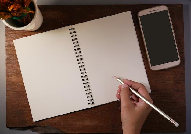 Mulher, mãos, escrita, caderno, lápis, smartphone, copo, secos, flor, madeira