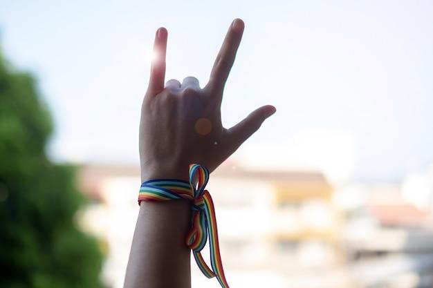 Mulher, mãos, mostrando, sinal amor, com, lgbtq, fita arco-íris