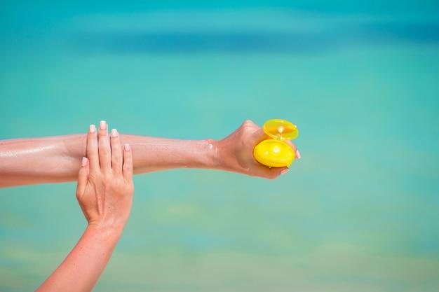Mulher, mãos, pôr, protetor solar, de, um, suncream, garrafa
