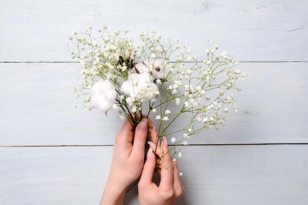 Mulher mãos segurando flores de monte sobre fundo azul de madeira.