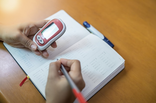 Mulher, mãos, segurando, medidor glucose, e, caneta uso, para, escreva, cronograma, cheque, nível açúcar sangue