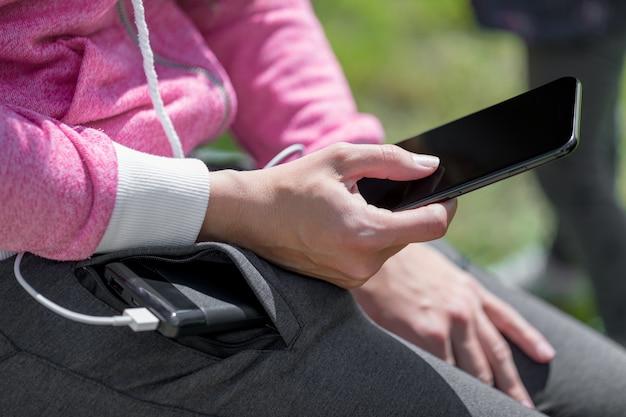 Mulher, mãos, segurando, pretas, smartphone, carregar, bateria, de, externo, poder, banco