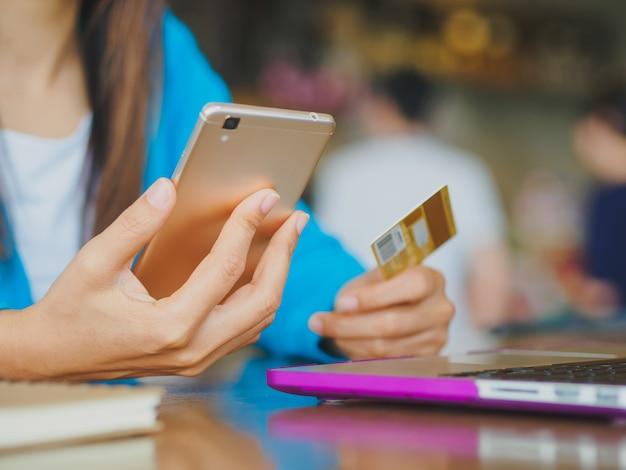 Mulher, mãos, segurando, um, cartão crédito, e, usando, smartphone, para, shopping online