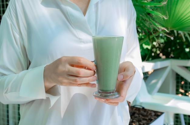 Mulher mãos segurar copo verde matcha latte café chá vidro vidro folhas tropical