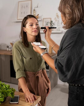 Mulher maquiando uma atriz para um filme