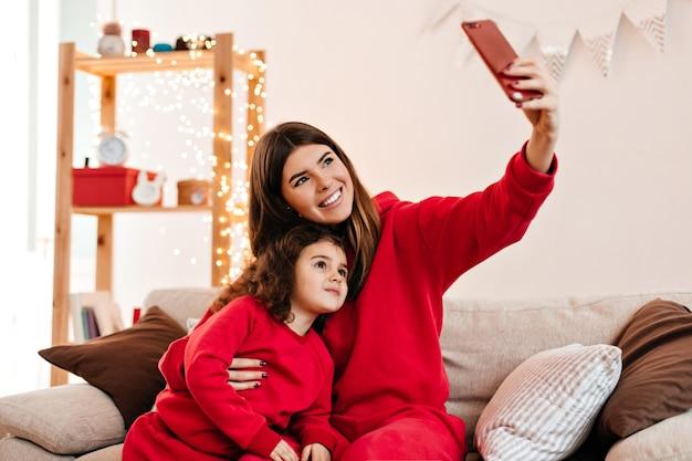 Mulher maravilhosa, abraçando a filha e tomando selfie. tiro interno da feliz mãe segurando o smartphone.