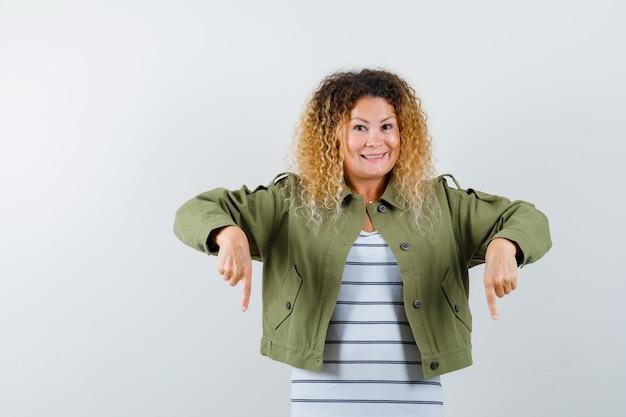 Mulher maravilhosa apontando para baixo enquanto sorria com jaqueta verde, camisa e olhando alegre, vista frontal.