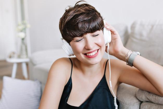 Mulher maravilhosa com cabelo castanho brilhante curtindo sua música favorita com os olhos fechados e sorriso sentada ao lado do sofá