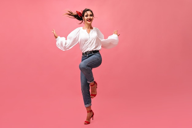 Mulher maravilhosa de bom humor, dançando no fundo rosa. senhora sorridente na blusa de mangas largas e sapatos vermelhos, posando em pano de fundo isolado.