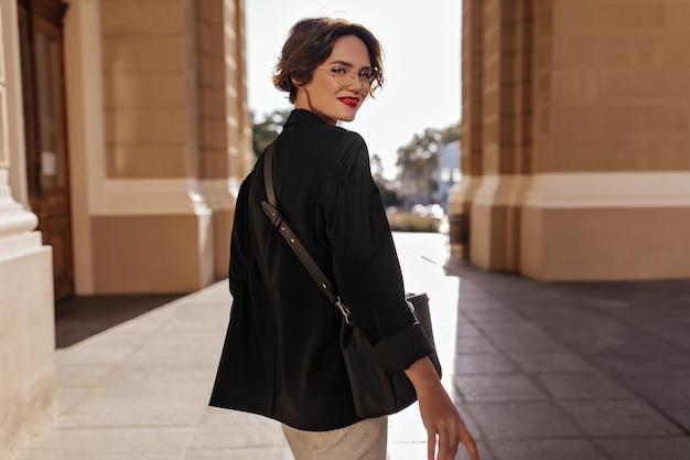 Mulher maravilhosa na jaqueta preta com bolsa escura, sorrindo para a rua. mulher de cabelo curto em óculos com lábios vermelhos, posando do lado de fora.