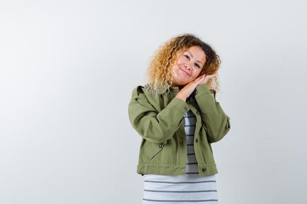 Mulher maravilhosa na jaqueta verde, camisa inclinando a bochecha nas mãos e olhando otimista, vista frontal.