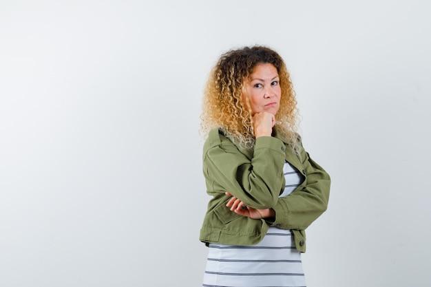 Mulher maravilhosa na jaqueta verde, camisa, mantendo a mão no queixo e parecendo preocupada, vista frontal.