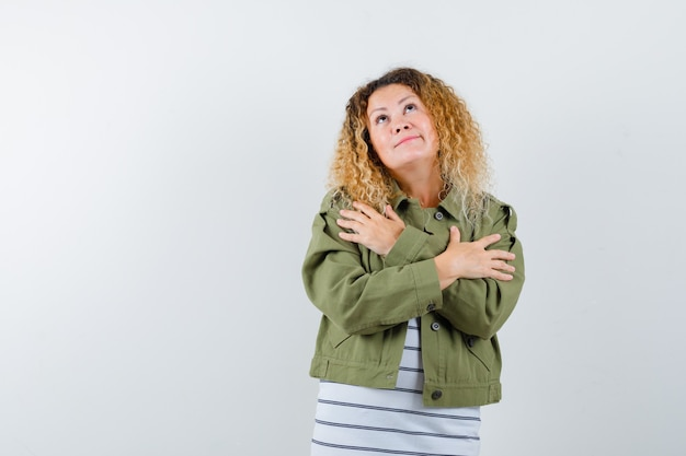 Mulher maravilhosa na jaqueta verde, camisa se abraçando e parecendo preocupada, vista frontal.