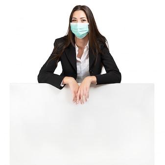 Mulher mascarada, apoiando-se em um sinal, propaganda durante a pandemia de coronavírus, isolada no branco