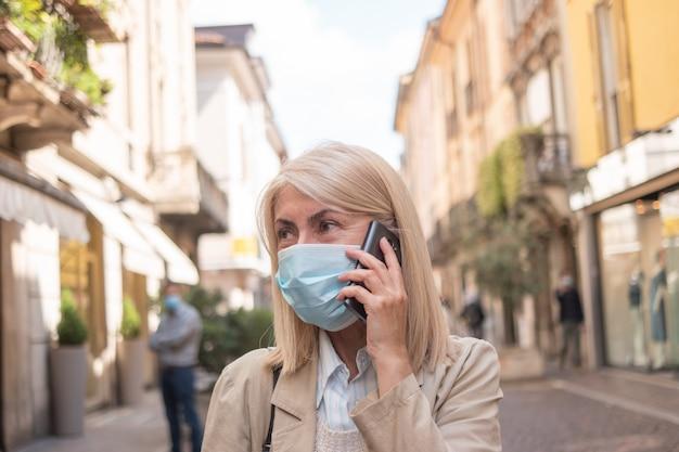 Mulher mascarada falando ao telefone enquanto caminhava em uma rua da cidade durante uma pandemia de coronavírus