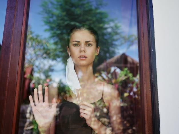 Mulher mascarada olhando pela janela proibição de bloqueio