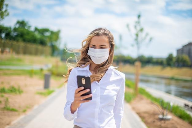 Mulher mascarada usando seu telefone celular em um parque
