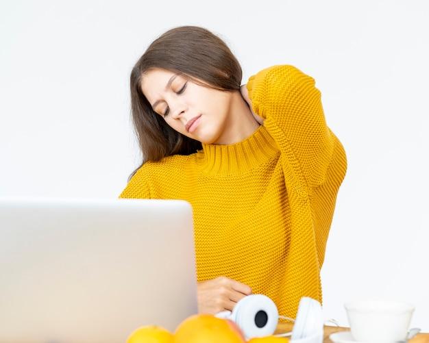 Mulher massageando a dor de garganta de trabalhar no computador por muito tempo. linda jovem de macacão amarelo brilhante sentada na mesa