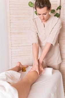 Mulher massageando a perna do cliente