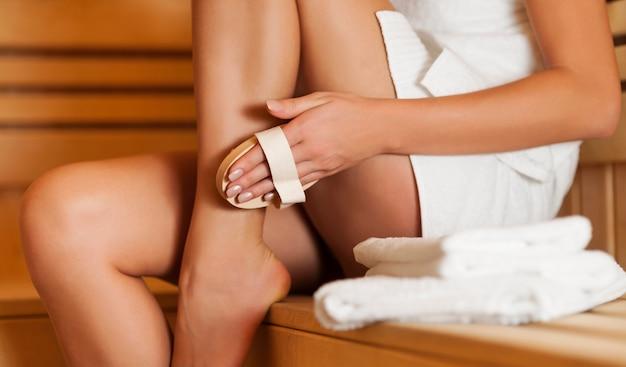 Mulher massageando a perna na sauna