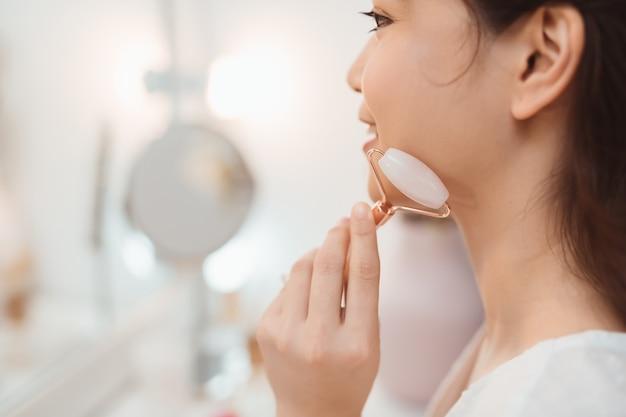 Mulher massageando o rosto com rolo facial de quartzo rosa. face lift, conceito de tratamento anti-envelhecimento. copie o espaço
