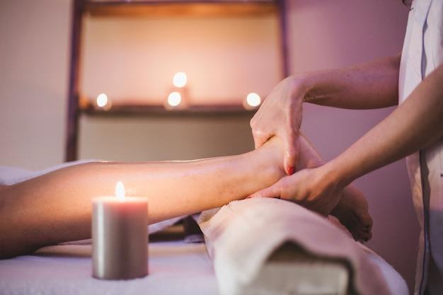 Mulher massageando os pés do cliente