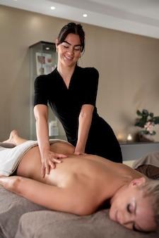 Mulher massageando seu cliente em seu salão
