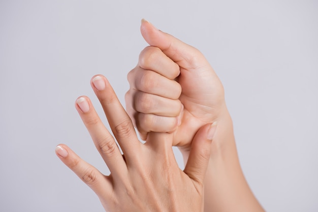 Mulher massageando seu doloroso dedo indicador.